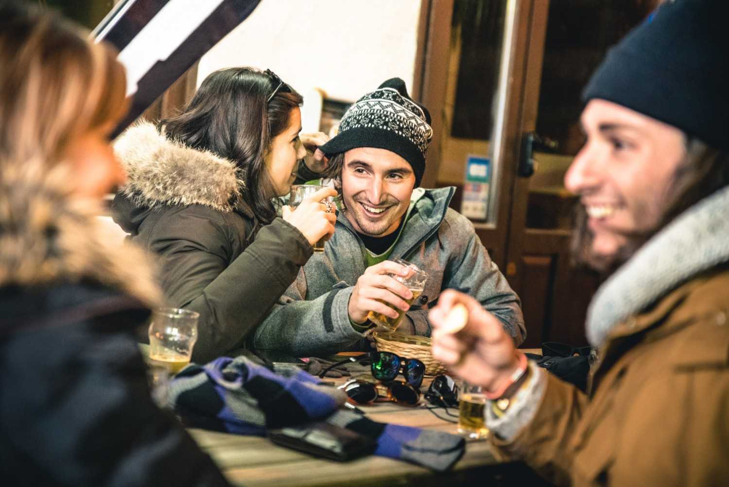 Happy friends drinking beer and eating chips by night at the Ullr Fest in Breckenridge, CO